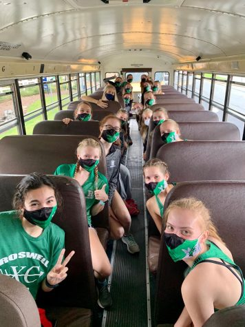 Although different from past seasons, the girls cross country team happily sits one to a seat on the bus and wear their masks in order to abide by safety guidelines.