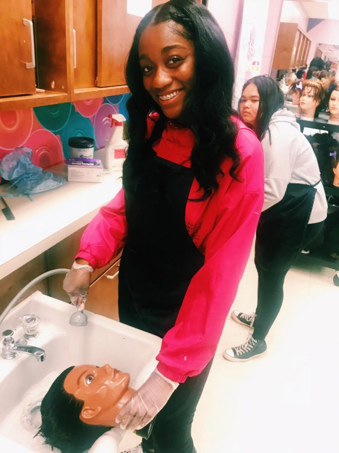 Haylee Sterling enjoys practicing hair care techniques in class Credit: Jakai Spikes