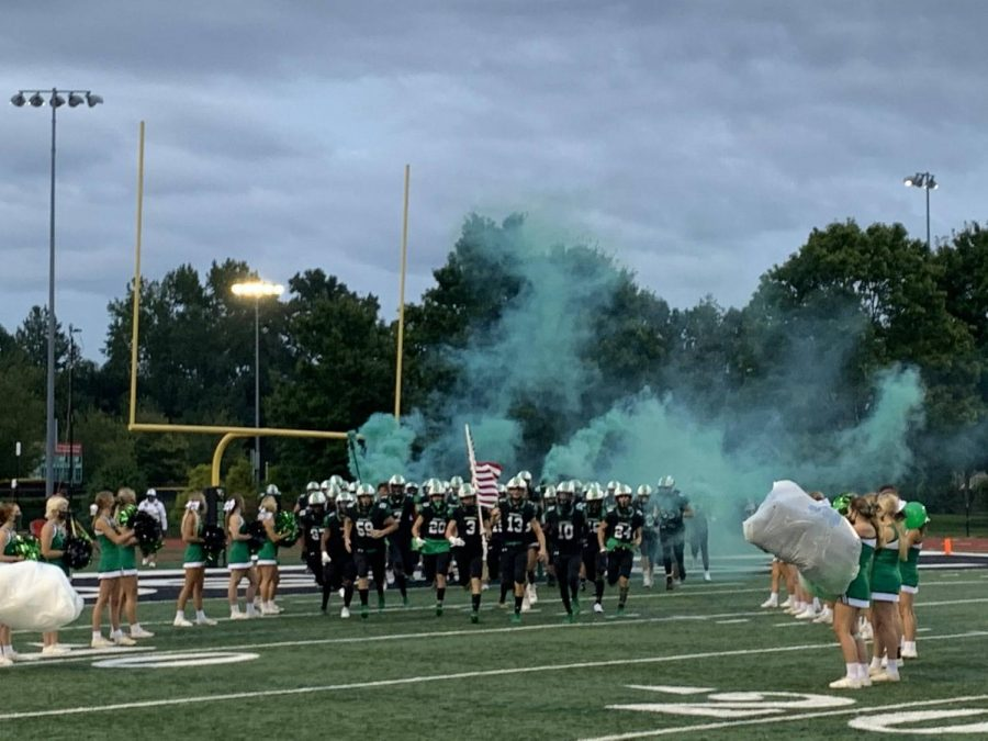 The Roswell Varsity Hornets take the field for their opening game against the Centennial Knights on September 18, 2020. Carrying the flag is Evan Plunkett (12). The Hornets defeated the Knights 42-13.