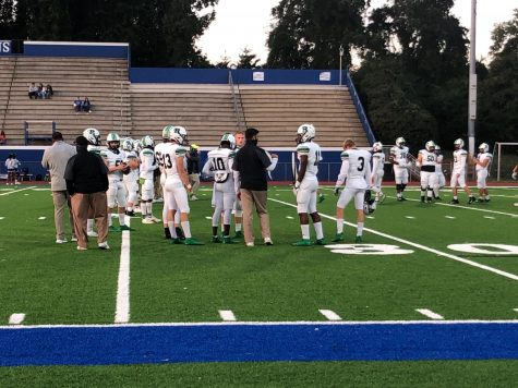 Varsity football players and coaches discuss their game plan during warmups.  Photo credit: Mady Agostini
