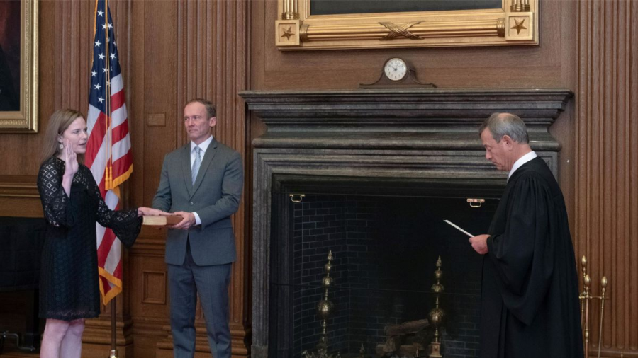 Chief Justice John G. Roberts is performing the swearing-in ceremony to Judge Amy Coney Barrett in the Supreme      court building, while Jesse M. Barrett holds the bible.  Credit: CNN