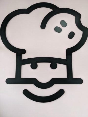 The Crumbl logo is a chef and is featured on the wall inside the building. Photo Credit: Ansley Tanner